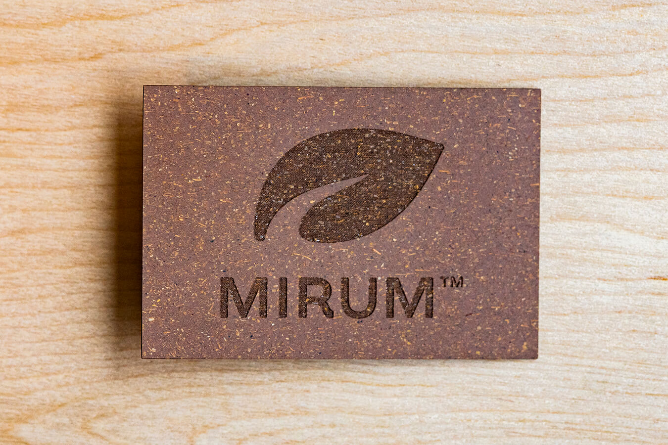 A MIRUM patch on a wooden surface. The patch displays the MIRUM logo.