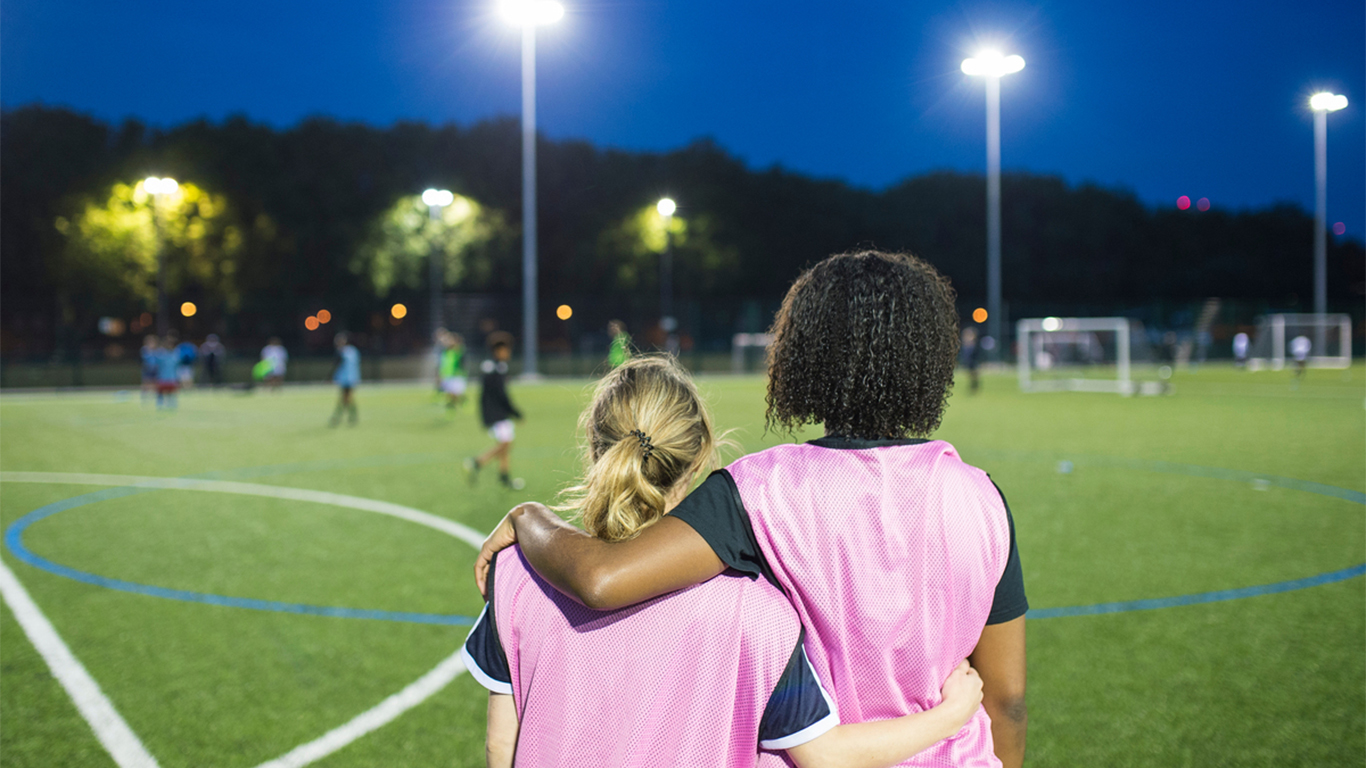 Two young soccer teammates look on at an ongoing game.